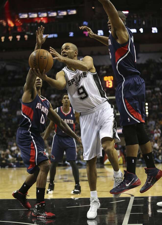 San Antonio Spurs' Tony Parker splits the defense of Atlanta Hawks' Jeff Teague, left, and Al Horford during the first half at the AT&T Center, Monday, Dec. 2, 2013. Photo: Jerry Lara, San Antonio Express-News