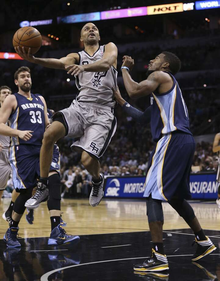 San Antonio Spurs' Tony Parker splits the defense of Memphis Grizzlies' Marc Gasol, left, and Mike Conley during the first half at the AT&T Center, Wednesday, Oct. 30, 2013. Photo: Jerry Lara, San Antonio Express-News