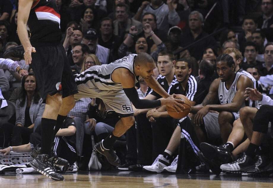 Patty Mills (8) of the San Antonio Spurs attempts to save a ball from going out of bounds by the team's bench during second-half NBA action against the Portland Trailblazers in the AT&T Center on Friday, Jan. 17, 2014. The Trailblazers won, 109-100. Photo: Billy Calzada, San Antonio Express-News