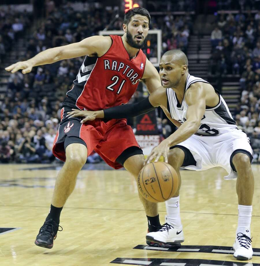 San Antonio Spurs' Patty Mills looks for room around Toronto Raptors' Greivis Vasquez during first half action Monday Dec. 23, 2013 at the AT&T Center. Photo: Edward A. Ornelas, San Antonio Express-News