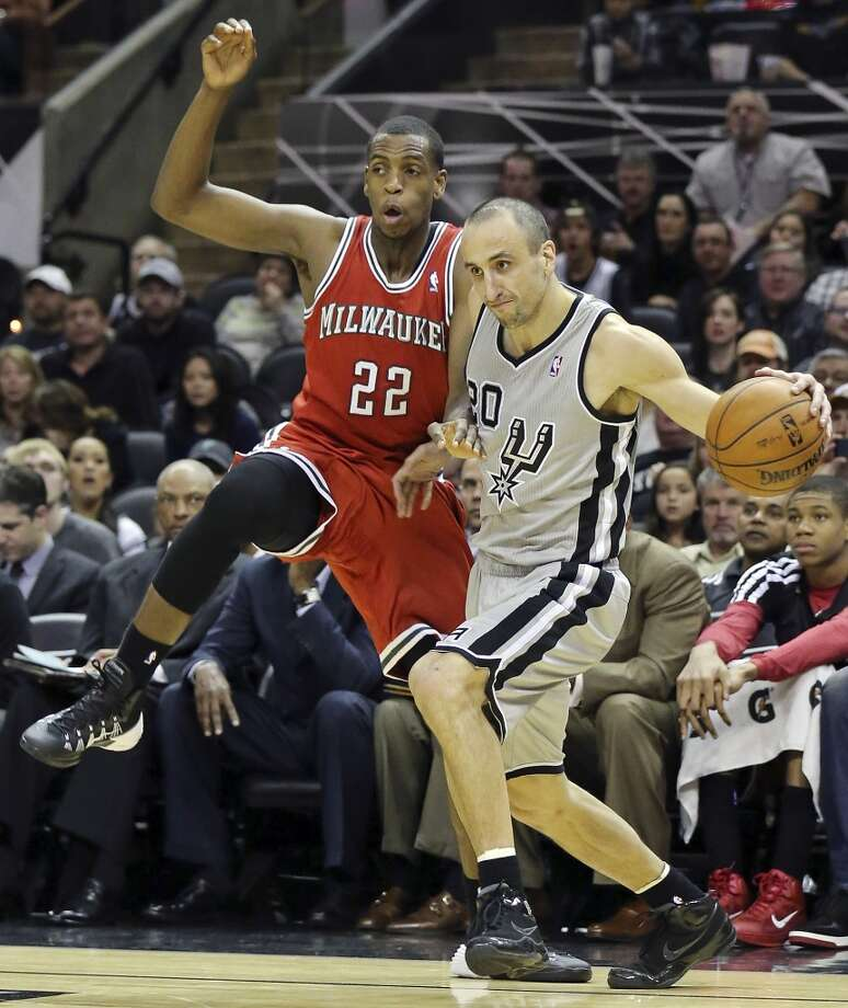 San Antonio Spurs' Manu Ginobili looks for room around Milwaukee Bucks' Khris Middleton during second half action Sunday Jan. 19, 2014 at the AT&T Center. The Spurs won 110-82. Photo: Edward A. Ornelas, San Antonio Express-News