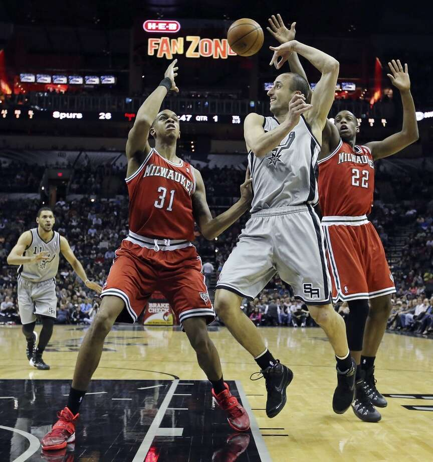 San Antonio Spurs' Manu Ginobili pass to Jeff Ayres between Milwaukee Bucks' John Henson (left) and Milwaukee Bucks' Khris Middleton during first half action Sunday Jan. 19, 2014 at the AT&T Center. Photo: Edward A. Ornelas, San Antonio Express-News