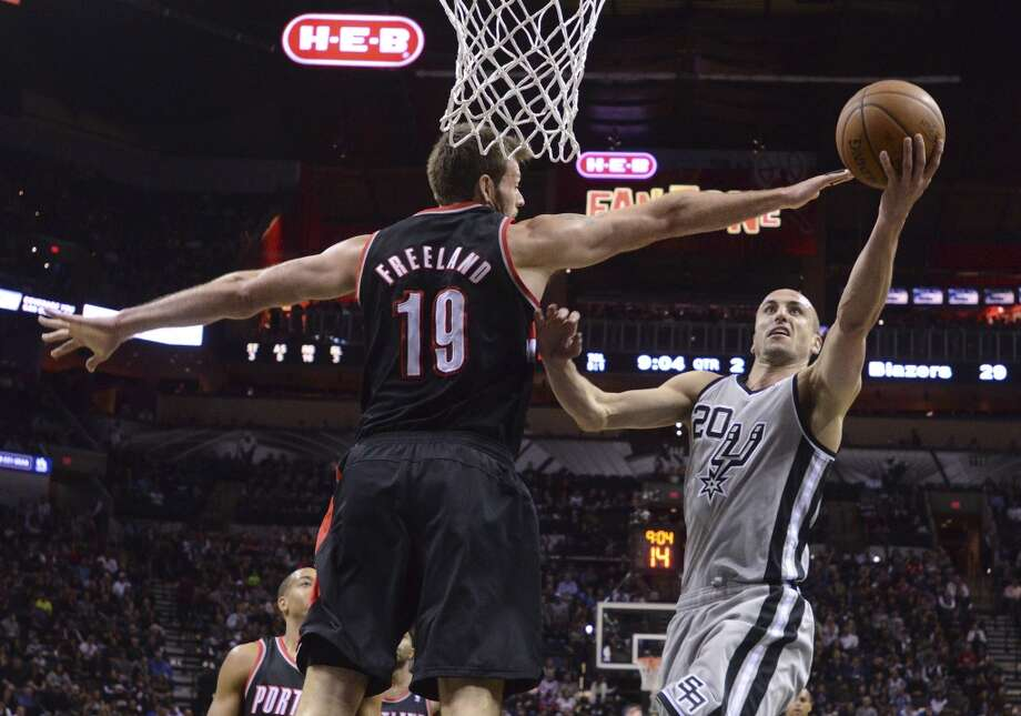 Manu Ginobili (20) of the San Antonio Spurs lays up the ball as Joel Freeland (19) of the Portland Trailblazers defends during NBA action in the AT&T Center on Friday, Jan. 17, 2014. Photo: Billy Calzada, San Antonio Express-News