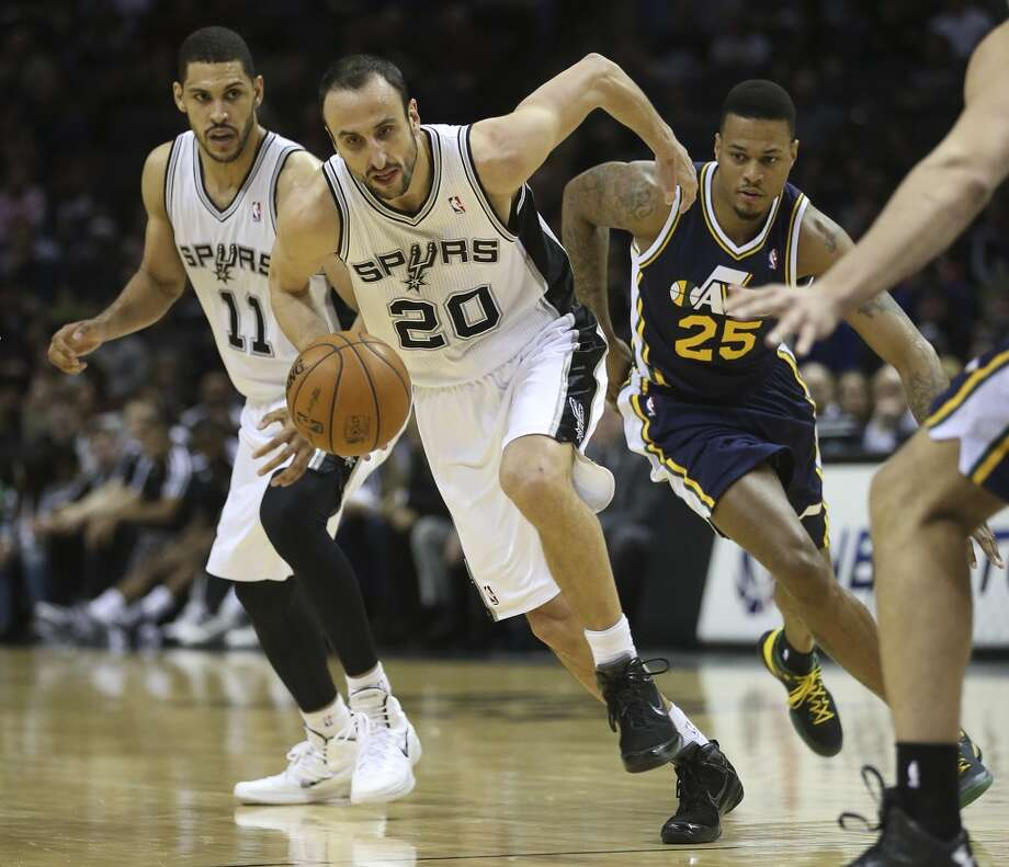 San Antonio Spurs' Manu Ginobili drives the ball as Utah Jazz' Brandon Rush chases during the first half at the AT&T Center, Wednesday, Jan. 15, 2014. In back is Jeff Ayres. Photo: Jerry Lara, San Antonio Express-News