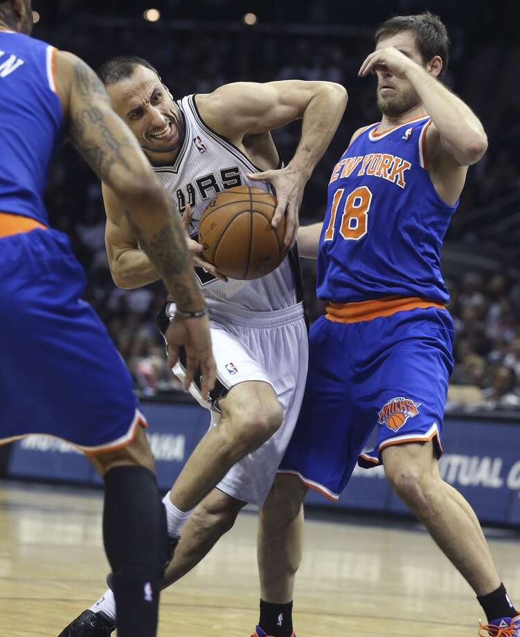 Manu Ginobili crunches into the lane against Beno Udrih ast he Spurs host the New York Knicks at the AT&T Center on January 2, 2014. Photo: Tom Reel, San Antonio Express-News