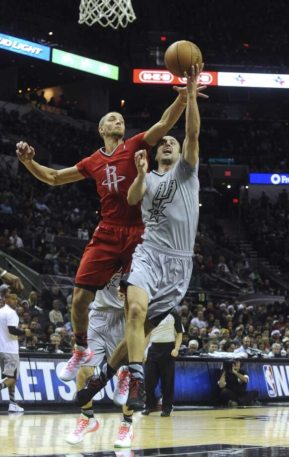 Manu Ginobili of the San Antonio Spurs is fouled by Chandler Parsons of the Houston Rockets during NBA action at the AT&T Center on Wednesday, Dec. 25, 2013. Ginobili made the ensuing free throws. Photo: Billy Calzada, San Antonio Express-News