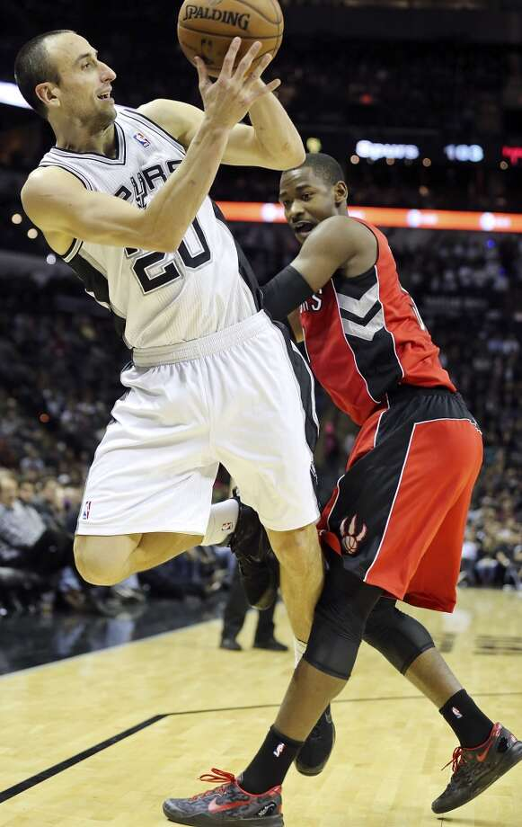 San Antonio Spurs' Manu Ginobili is fouled by Toronto Raptors' Terrence Ross during second half action Monday Dec. 23, 2013 at the AT&T Center. The Spurs won 112-99. Photo: Edward A. Ornelas, San Antonio Express-News