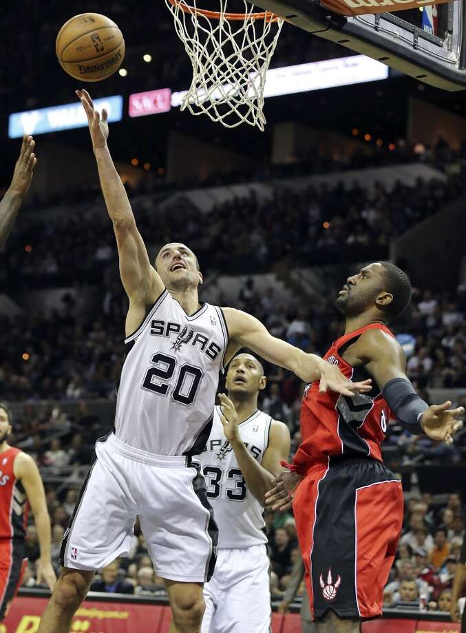 San Antonio Spurs' Manu Ginobili shoots around Toronto Raptors' Patrick Patterson during second half action Monday Dec. 23, 2013 at the AT&T Center. The Spurs won 112-99. Photo: Edward A. Ornelas, San Antonio Express-News
