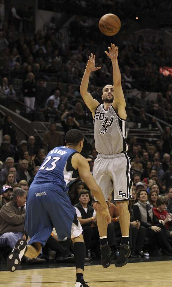 Spurs' Manu Ginobili (20) shoots a three-pointer against Minnesota Timberwolves' Kevin Martin (23) to put the Spurs up by one late in the fourth quarter at the AT&T Center on Friday, Dec. 13, 2013. Spurs defeated the T'Wolves, 117-110. Photo: Kin Man Hui, San Antonio Express-News