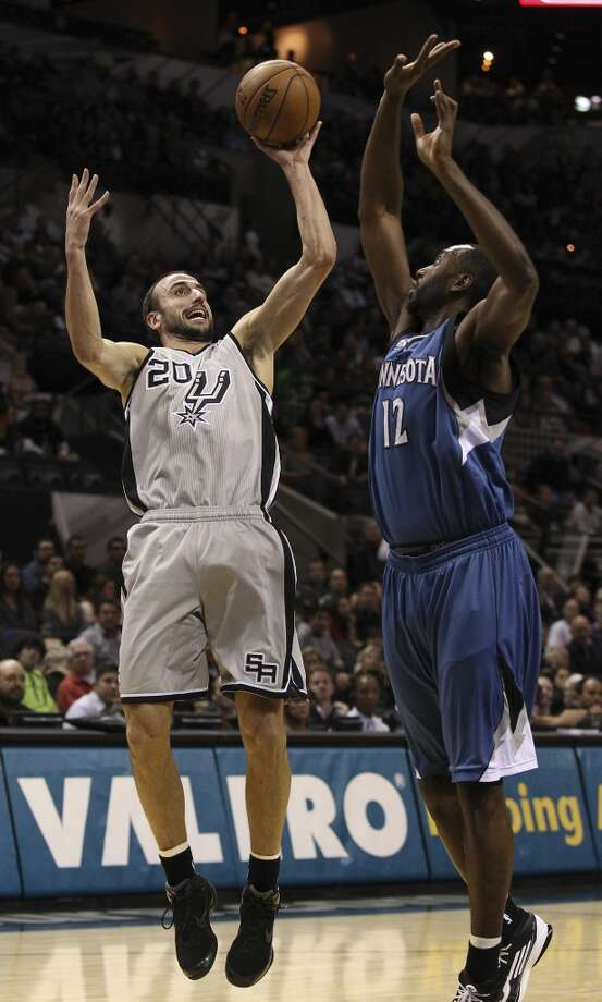 Spurs's Manu Ginobili (20) takes a shot against Minnesota Timberwolves' Luc Mbah a Moute (12) in the first half at the AT&T Center on Friday, Dec. 13, 2013. (Kin Man Hui/San Antonio Express-News) Photo: Kin Man Hui, San Antonio Express-News