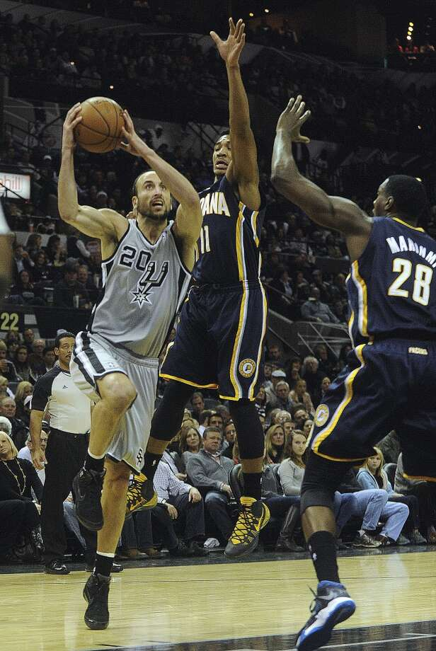 Manu Ginobili of the San Antonio Spurs drives before dishing off the ball as Orlando Johnson (11) and Ian Mahinmi of the Indiana Pacers defend during NBA action in the AT&T Center on Saturday, Dec. 7, 2013. Photo: Billy Calzada, San Antonio Express-News
