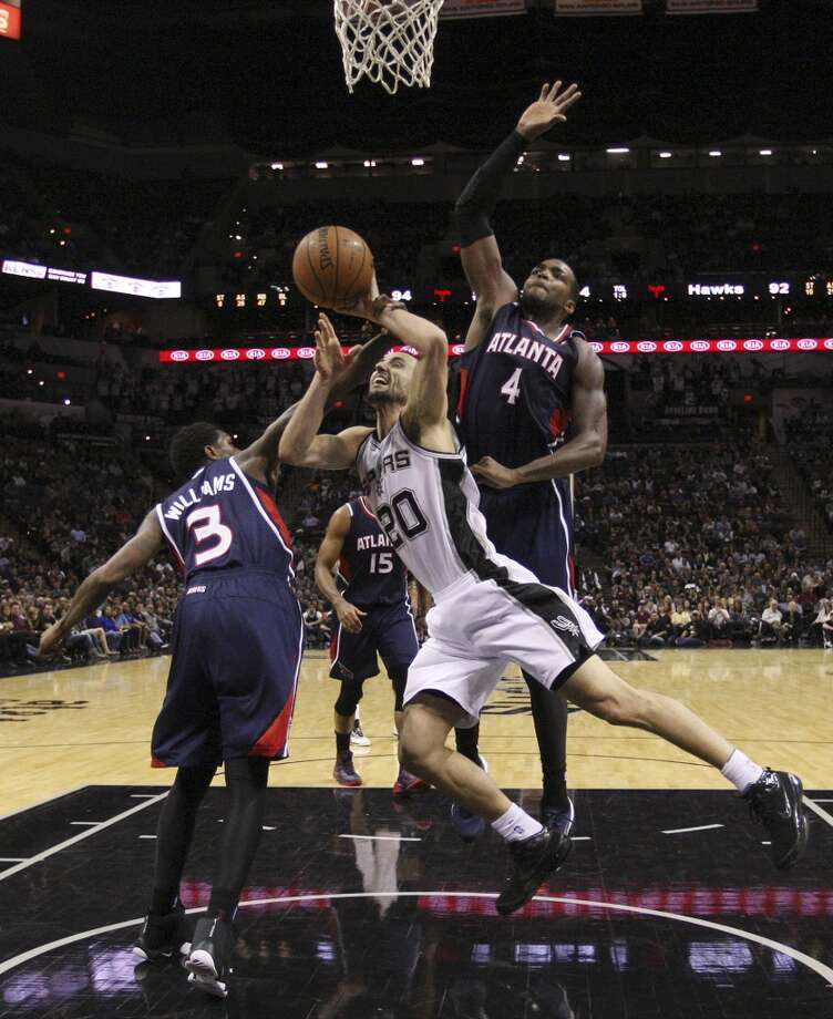 San Antonio Spurs' Manu Ginobili is defended by Atlanta Hawks' Louis Williams, left,  as Paul Millsap assists during the second half at the AT&T Center, Monday, Dec. 2, 2013. The Spurs won 102-100. Photo: Jerry Lara, San Antonio Express-News