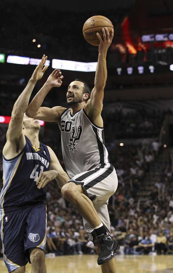 Spurs' Manu Ginobili (20) drives to the basket against Memphis Grizzlies' Kosta Koufos (41) at the home opener at the AT&T Center on Wednesday, Oct. 30, 2013. Spurs defeated the Grizzlies, 101-94. Photo: Kin Man Hui, San Antonio Express-News