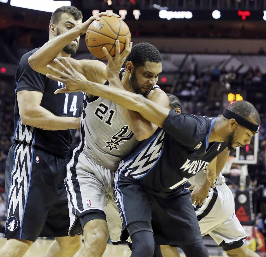 San Antonio Spurs' Tim Duncan looks for room between Minnesota Timberwolves' Nikola Pekovic (left) and Corey Brewer during first half action Sunday Jan. 12, 2014 at the AT&T Center. Photo: Edward A. Ornelas, San Antonio Express-News