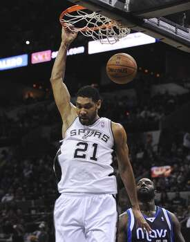 Tim Duncan of the San Antonio Spurs dunks as DeJuan Blair of the Dallas Mavericks watches during second-half NBA action at the AT&T Center on Wednesday, Jan. 8, 2014. Photo: Billy Calzada, San Antonio Express-News