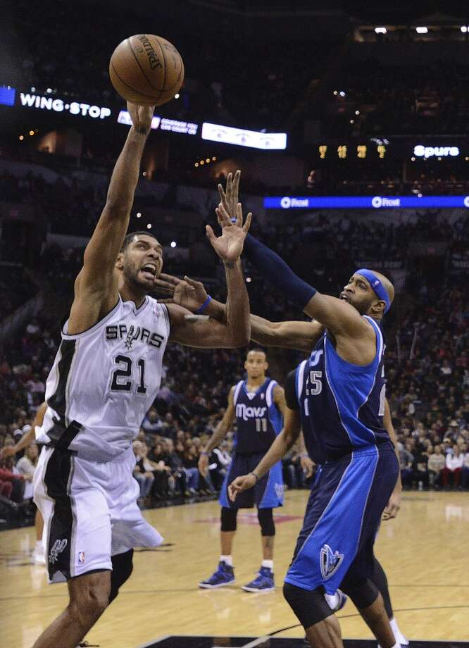 The San Antonio Spurs' Tim Duncan (21) shoots as Vince Carter of the Dallas Mavericks defends  during second-half NBA action at the AT&T Center on Wednesday, Jan. 8, 2014. The Spurs won the game, 120-90. Photo: Billy Calzada, San Antonio Express-News