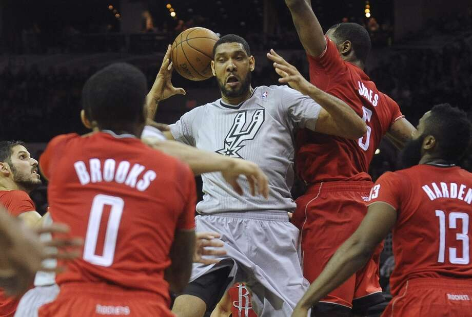 Tim Duncan of the San Antonio Spurs comes up with the ball against the Houston Rockets during second-half NBA action at the AT&T Center on Wednesday, Dec. 25, 2013. Duncan controlled the ball and was able to shoot a layup to score. Photo: Billy Calzada, San Antonio Express-News