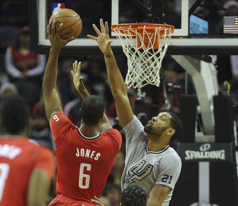 Terrence Jones of the Houston Rockets shoots as Tim Duncan of the San Antonio Spurs defends during NBA action at the AT&T Center on Wednesday, Dec. 25, 2013. Photo: Billy Calzada, San Antonio Express-News