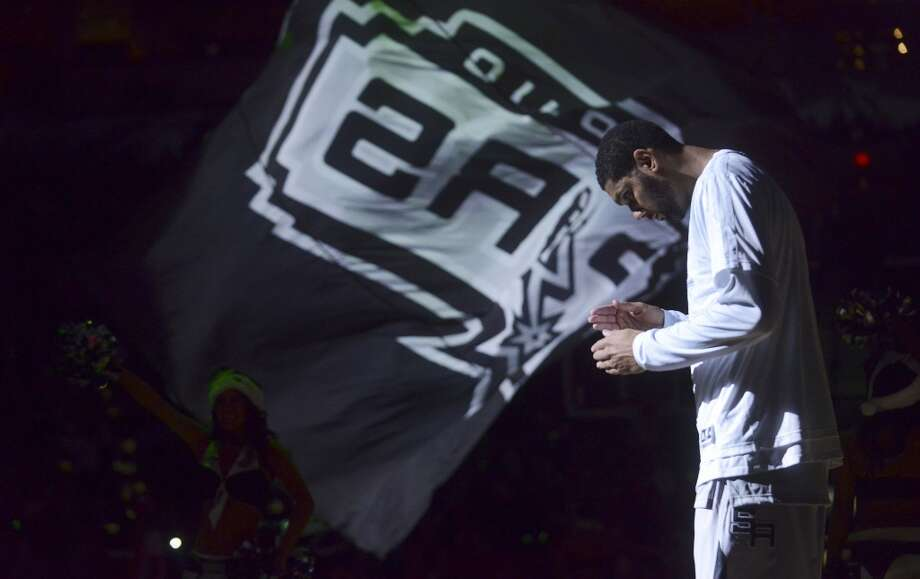 Tim Duncan of the San Antonio Spurs stands in the spotlight after being introduced before the team's game against the Houston Rockets at the AT&T Center on Wednesday, Dec. 25, 2013. Photo: Billy Calzada, San Antonio Express-News