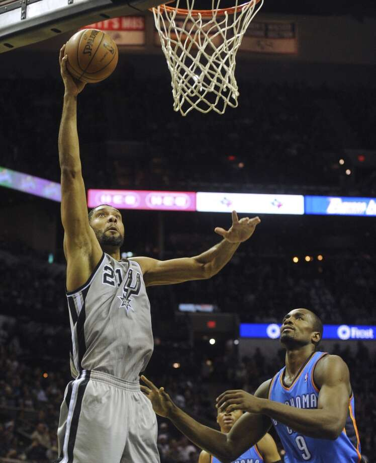 Tim Duncan of the San Antonio Spurs dunks the ball over Serge Ibaka of the Oklahoma City Thunder during first-half NBA action at the AT&T Center on Saturday, Dec. 21, 2013. Photo: Billy Calzada, San Antonio Express-News