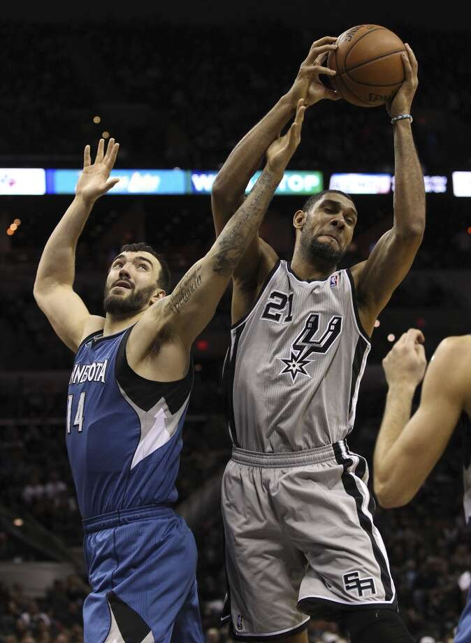 Spurs' Tim Duncan (21) grabs a rebound against Minnesota Timberwolves' Nikola Pekovic (14) in the second half at the AT&T Center on Friday, Dec. 13, 2013. Spurs defeated the T'Wolves, 117-110. Photo: Kin Man Hui, San Antonio Express-News