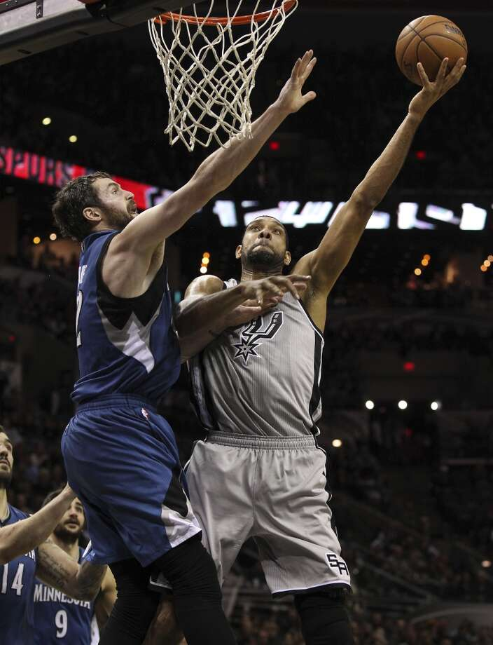 Spurs' Tim Duncan (21) shoots against Minnesota Timberwolves' Kevin Love (42) in the second half at the AT&T Center on Friday, Dec. 13, 2013. Spurs defeated the T'Wolves, 117-110. Photo: Kin Man Hui, San Antonio Express-News