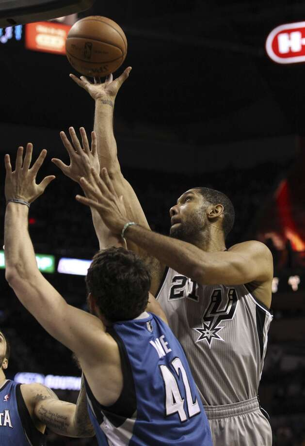 Spurs' Tim Duncan (21) shoots against Minnesota Timberwolves' Kevin Love (42) in the first half at the AT&T Center on Friday, Dec. 13, 2013. Photo: Kin Man Hui, San Antonio Express-News