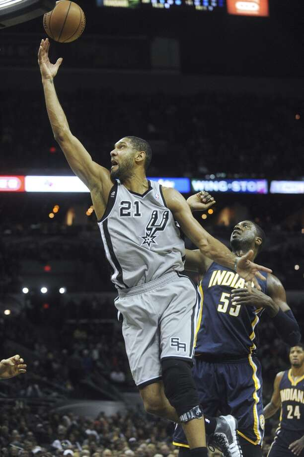 Tim Duncan of the San Antonio Spurs lays up a shot as Roy Hibbert of the Indiana Pacers gives chase during first-half NBA action in the AT&T Center on Saturday, Dec. 7, 2013. Photo: Billy Calzada, San Antonio Express-News