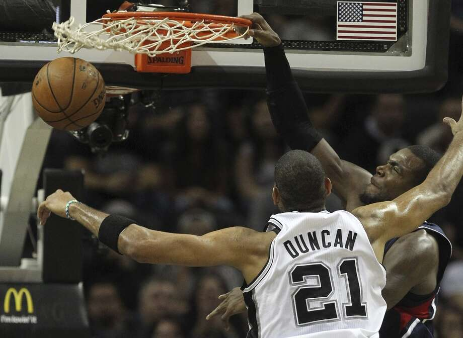 Atlanta Hawks' Paul Millsap dunks over San Antonio Spurs' Tim Duncan during the second half at the AT&T Center, Monday, Dec. 2, 2013. The Spurs won 102-100. Photo: Jerry Lara, San Antonio Express-News