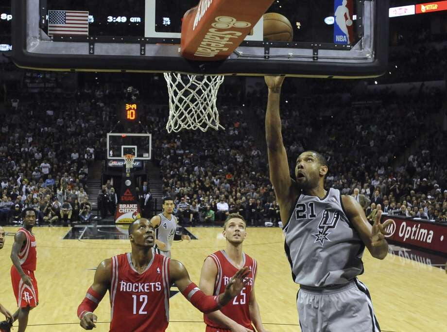 Tim Duncan of the San Antonio Spurs, right, hits on a layup as Dwight Howard (12) and Chandler Parsons defend during second-half NBA action at the AT&T Center on Saturday, Nov. 30, 2013. Photo: Billy Calzada, San Antonio Express-News