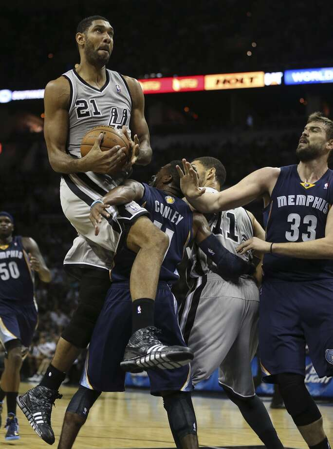 San Antonio Spurs' Tim Duncan goes over Memphis Grizzlies' Mike Conley during the first half at the AT&T Center, Wednesday, Oct. 30, 2013. Photo: Jerry Lara, San Antonio Express-News