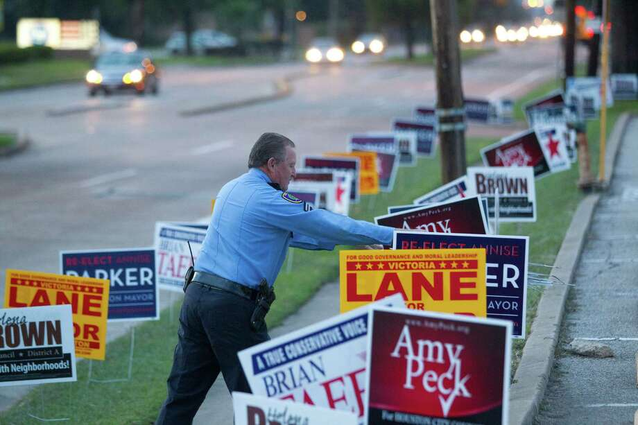 "HPD officer J.J. Mounsey removes candidate bandit signs from the city easement area between the sidewalk and the street outside an early voting site at the Trini Mendenhall Sosa Community Center Monday, Oct. 21, 2013, in Houston.  Officer Mounsey said he had already received complaints about the signs, which are not supposed to be on grassy area on the street side of the sidewalk.  ""People can't see when they try to pull out in their cars,"" he said.  ( Johnny Hanson / Houston Chronicle ) Photo: Johnny Hanson, Staff / Houston Chronicle"