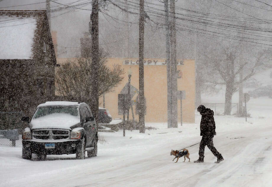 As the snow flies, a man crosses with his dog on Merwin Avenue in Milford, Conn. on Tuesday January 21, 2014. Photo: Christian Abraham / Connecticut Post