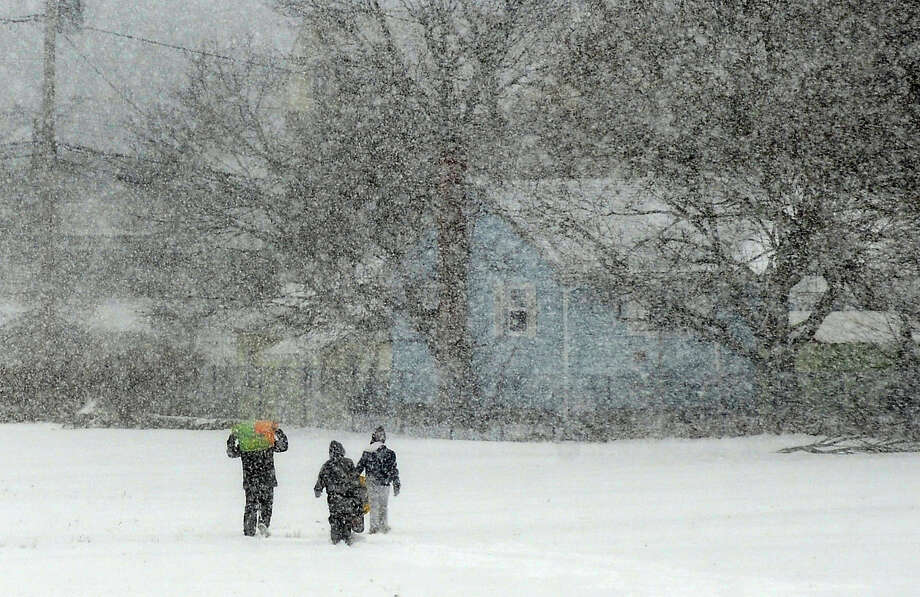 Kids make their way back home from a park off of Melba Street in Milford, Conn. as a snowstorm hits the reagion on Tuesday January 21, 2014. Photo: Christian Abraham / Connecticut Post