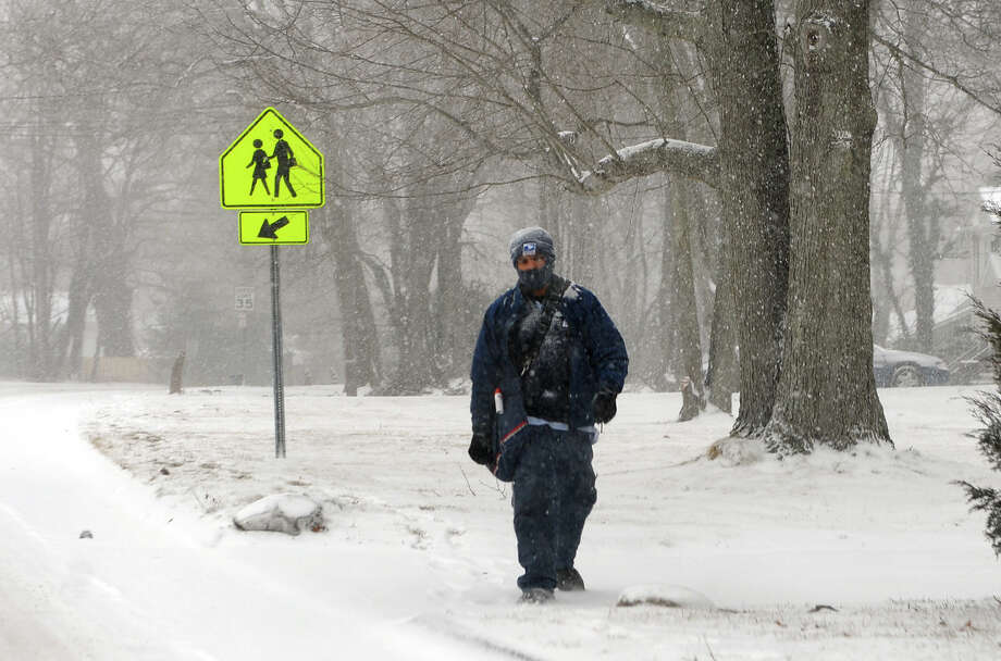 A postal worker trudges along as a snowstorm hits the region in Milford, Conn. on Tuesday January 21, 2014. Photo: Christian Abraham / Connecticut Post