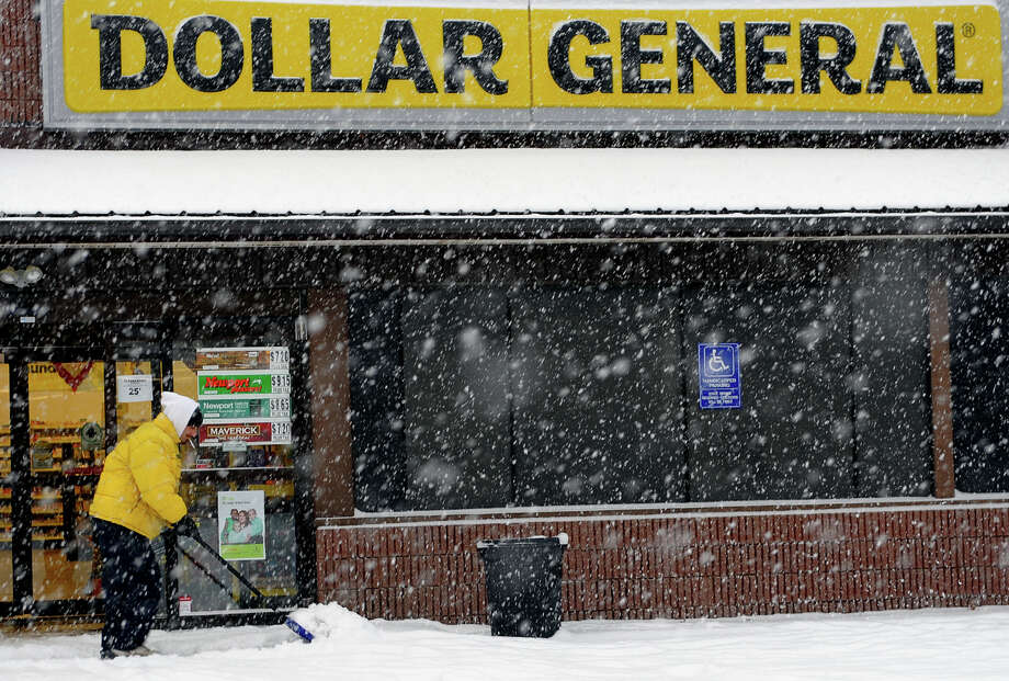 Bryan Musicus, of Pete's Water Garden and Landscape Creations, shovels snow in front of the Dollar General store as a snowstorm hits the reagion in Milford, Conn. on Tuesday January 21, 2014. Photo: Christian Abraham / Connecticut Post