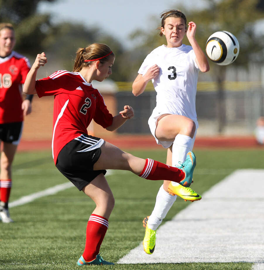 Steele's Angelica Durland, right, tries to block a kick by New Braunfels Canyon's Gloriana Durbin during their match Friday in the Steele Showcase 2014 tournament.  Canyon jumped off to an early lead and held off the Lady Knights, 2-1. Photo: Marvin Pfeiffer / NE Herald / Prime Time Newspapers 2014