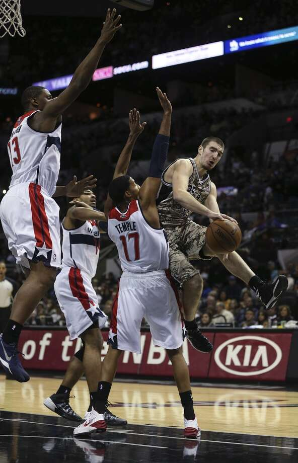 San Antonio Spurs' Nando De Colo gets around a wall of Washington Wizards from left, Kevin Seraphin, Glen Rice and Garrett Temple during the second half at the AT&T Center, Wednesday, Nov. 13, 2013. The Spurs won 92-79. Photo: Jerry Lara, San Antonio Express-News