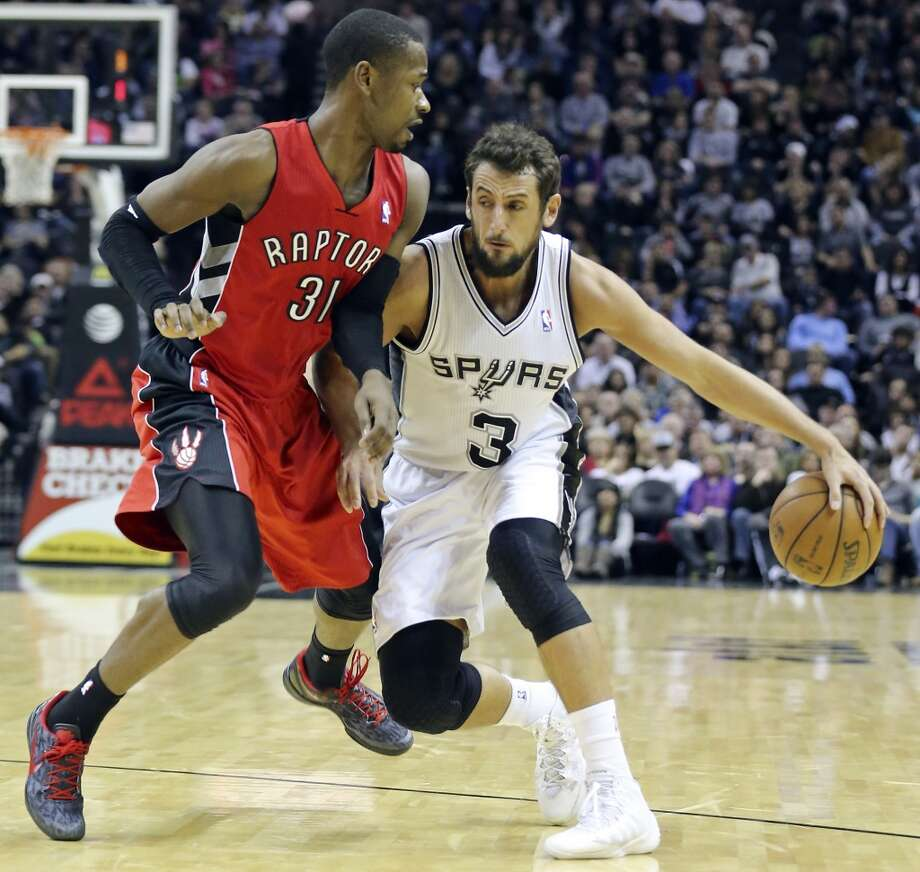 San Antonio Spurs' Marco Belinelli looks for room around Toronto Raptors' Terrence Ross during first half action Monday Dec. 23, 2013 at the AT&T Center. Photo: Edward A. Ornelas, San Antonio Express-News