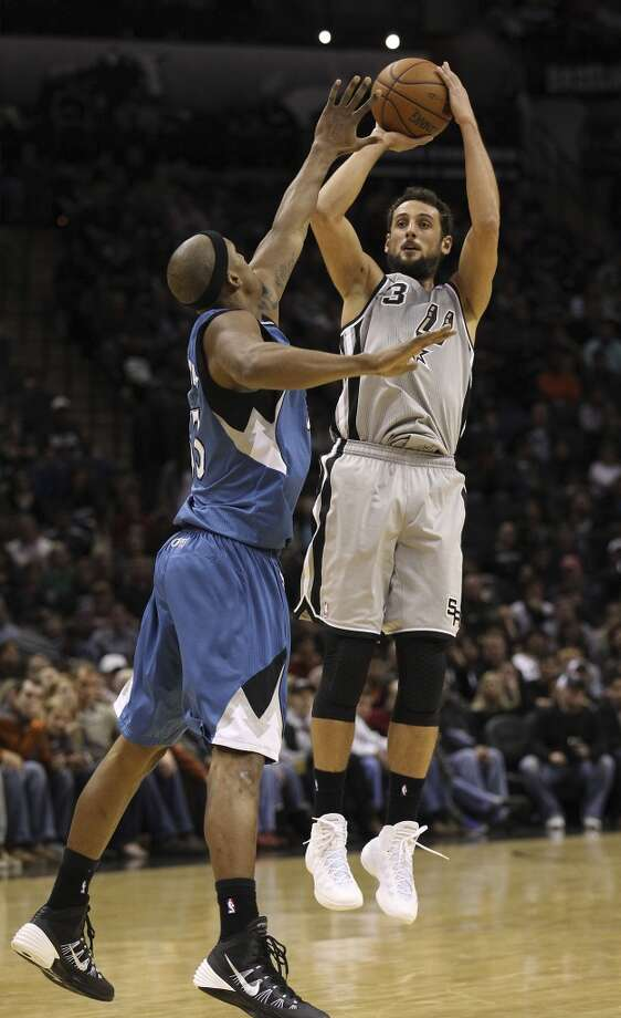 Spurs' Marco Belinelli (03) hoists a shot up against Minnesota Timberwolves' Dante Cunningham (33) in the second half at the AT&T Center on Friday, Dec. 13, 2013. Spurs defeated the T'Wolves, 117-110. Photo: Kin Man Hui, San Antonio Express-News