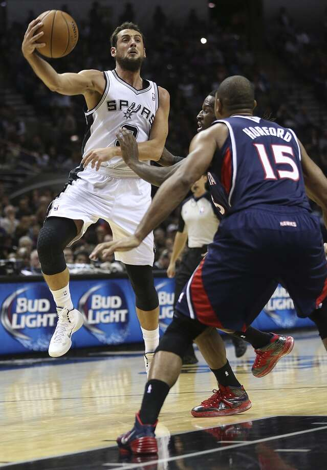 San Antonio Spurs' Marco Belinelli passes the ball out to the perimeter as Atlanta Hawks' Al Horford defends during the first half at the AT&T Center, Monday, Dec. 2, 2013. Photo: Jerry Lara, San Antonio Express-News