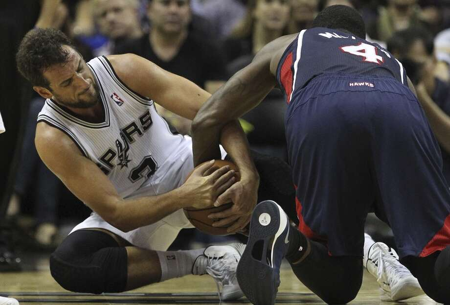 San Antonio Spurs' Marco Belinelli struggles for a loose ball against Atlanta Hawks' Paul Millsap during the second half at the AT&T Center, Monday, Dec. 2, 2013. The Spurs won 102-100. Photo: Jerry Lara, San Antonio Express-News