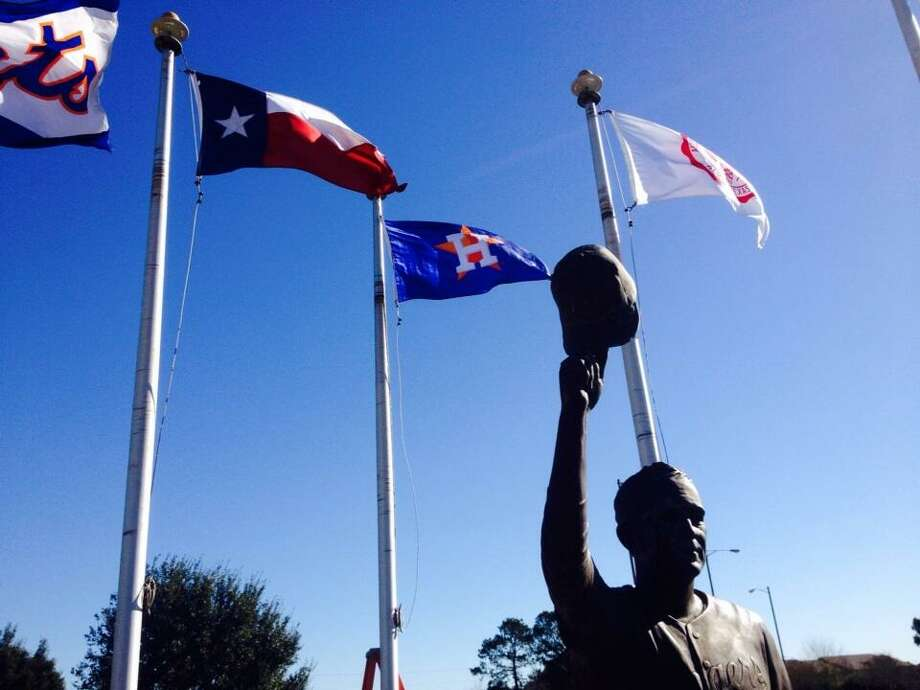 In the shadow of Nolan Ryan's statue, the Astros' flag was raised by Reid Ryan and Alvin officials. Photo: Jose De Jesus Ortiz, Houston Chronicle