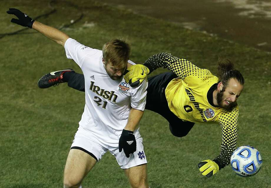 Notre Dame's Vince Cicciarelli (21) collides with New Mexico goalkeeper Michael Lisch (0) in the second half during a semifinal match in the  NCAA Division 1 men's soccer championships in Chester, Pa., Friday, Dec. 13, 2013. Notre Dame defeated New Mexico 2-0 to advance to Sunday's championship game. (AP Photo/Rich Schultz) Photo: Rich Schultz, Associated Press / FR27227 AP