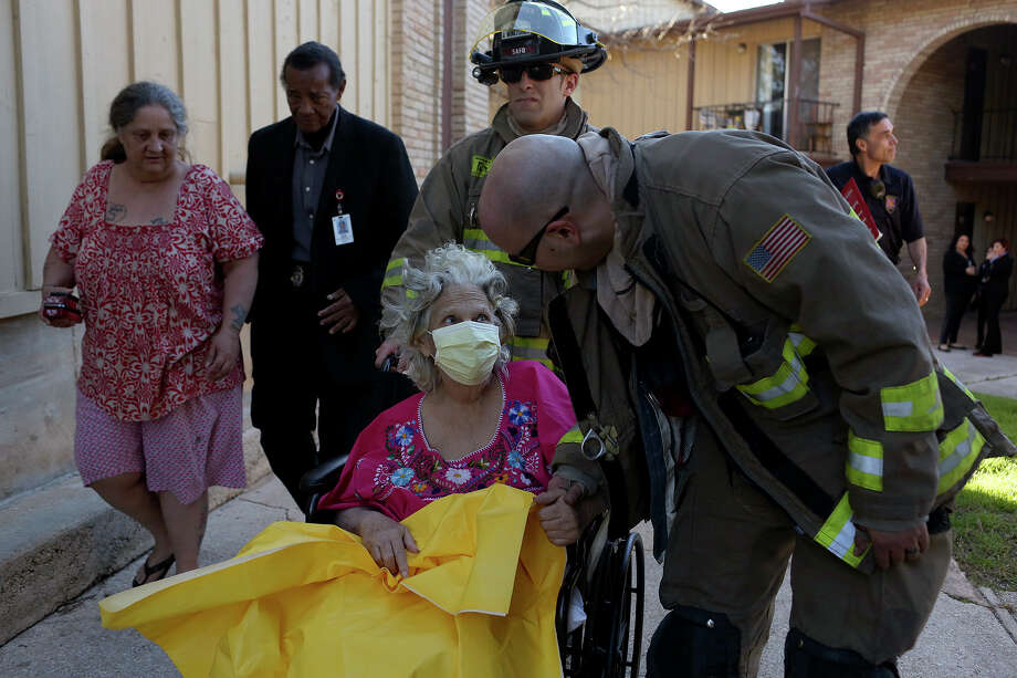 Kathleen Besch, 72, with her daughter, Catherine Holt, left, is helped by firefighters Jeremy Wuneburger, center, and Chris Espinoza, right, from Engine 23, back to her apartment after a fire in the building next to theirs forced them from their apartment at the La Fiesta Apartments on North Vandiver Road in San Antonio on Tuesday, Jan 21, 2014. Photo: Lisa Krantz, San Antonio Express-News / San Antonio Express-News