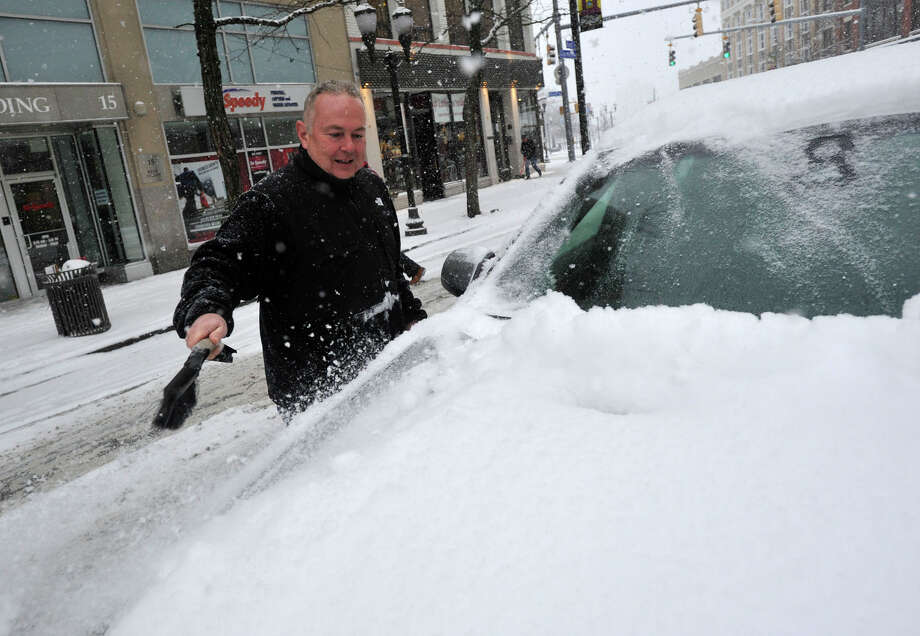 Harry Mascolo clears off snow and ice from his car in downtown Stamford, Conn., on Tuesday, Jan. 21, 2014. Photo: Jason Rearick / Stamford Advocate