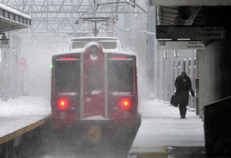 People walk along a Metro-North Railroad platform as a train exits the station blowing snow in its wake in Stamford, Conn., on Tuesday, Jan. 21, 2014. Photo: Jason Rearick / Stamford Advocate