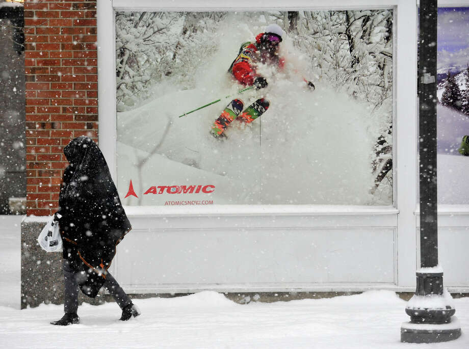 A woman covers her head from the snow while walking past an advertisement for Pedigree Ski Shop in downtown Stamford, Conn., on Tuesday, Jan. 21, 2014. Photo: Jason Rearick / Stamford Advocate