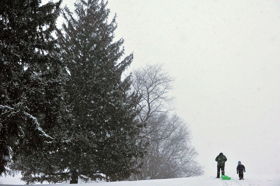Sean Flood, left, and his son, Jackson, make their way to the top of the hill before sledding back down it again at Brennan Golf Course in Stamford, Conn., on Tuesday, Jan. 21, 2014. Photo: Jason Rearick / Stamford Advocate