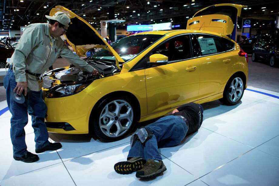 Benny Lopez, left, and James Quinn, right, work on the last details of setting up a 2014 Ford Focus five door hatchback for display at the Ford venue a day before the Houston Auto Show, Tuesday, Jan. 21, 2014, at Reliant Center in Houston. Photo: Marie D. De Jesus, Houston Chronicle / © 2014 Houston Chronicle